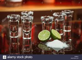 drink table bar two shots of tequila with lime and salt on a wooden table bar on