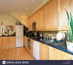 pale wood fitted units with granite worktops in modern kitchen
