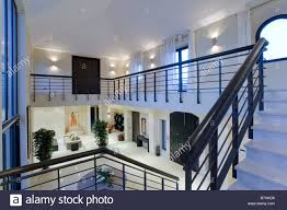 black metal bannisters and marble stairs in double height entrance