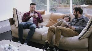 Same Sex Couple Family On The Couch Using Digital Tablet Stock - Family sex room