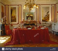 chandelier above table set for dinner with rich red cloth in