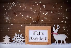 white decoration on snow feliz navidad means merry stock