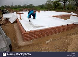 builder laying esp 100 polystyrene as highly insulated layer on
