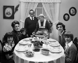 three generation family saying grace prayer at thanksgiving dinner
