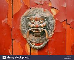 door knocker on an old red door at hutongs in beijing china stock