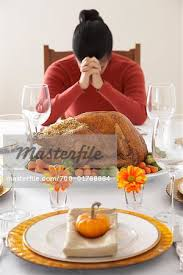 saying grace at thanksgiving dinner stock photo