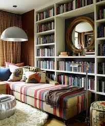 reading corner with bookcase and mirror and striped seating and