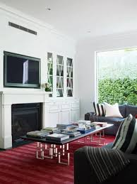 relaxed living room ambiance with grey sofa red rug fireplace and