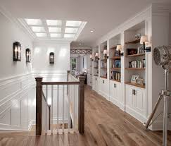 upper hallway built in bookshelves natural wood floors