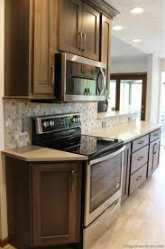 village home stores gray hickory stained bettendorf galley kitchen with whirlpool appliances villagehomestores