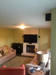 tv mounting over a limestone fireplace wall with wires concealed