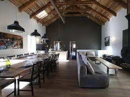canape loft taupe grand salon moderne mur gris charpente apparente moderne lustre