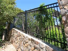 Metal Arbors Steel Fence On A Rock Wall By Arbor Fence Inc Iron Fencing