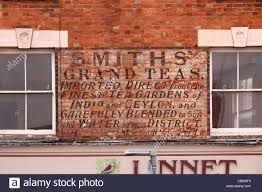 faded painted tea shop sign on brick wall above shop in