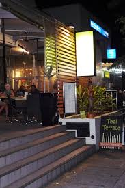 common view of thai terrace facade displaying dark glass wall and