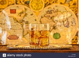 Ancient World Map by Whisky Glass On Silver Platter On Wooden Table With Ancient World
