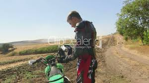 motocross bike videos young enduro racer dressing motorcycle protective gear beside his