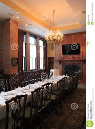 long dark wood table and chairs in dining room set for party