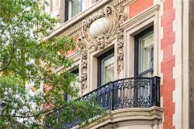 historic ues mansion with michael jackson and gossip girl ties which includes a bowed portico atop garland swaged columns a carved stone balcony two story bay window limestone quoins and red brick