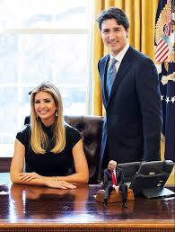tiny trump sits on a desk with ivanka trump and justin trudeau