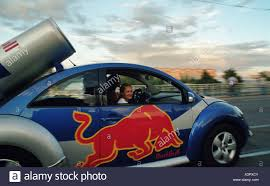volkswagen new beetle red volkswagen new beetle with an advertisement of red bull