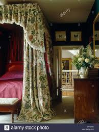 country bedroom with four poster bed with floral drapes and