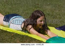 a young sliding on a backyard water slide stock photo