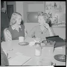 actress bette davis and daughter sitting at table together