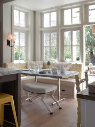 bright breakfast banquette love the windows and goat footed stool