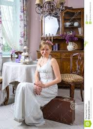 young in a retro style wedding dress is sitting on a suitca