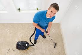 high angle view of happy worker vacuuming carpet stock photo