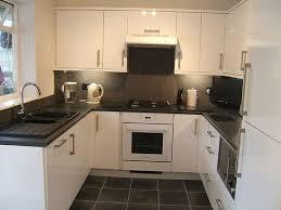 black worktop white cupboards kitchen monotone colour scheme white gloss kitchen black tiles