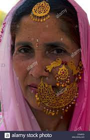 hindu nose ring women in beautiful indian dresses and gold jewelry stock photo