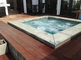 spa with poured in place concrete coping ipe wood deck and image