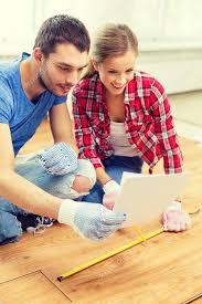 smiling measuring wood flooring stock photo