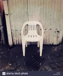 White Plastic Patio Chairs White Plastic Patio Chair Against Corrugated Metal Wall On A