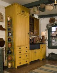 prim farmhouse kitchen with mustard cupboards and crocks