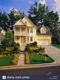front view of a large two story yellow house with white trim a