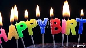 lighted candles on a happy birthday cake candles with the words