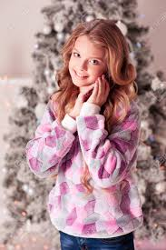 long hair on 66 year old smiling teen girl 12 15 year old posing over christmas tree in