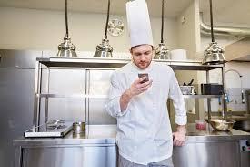 cuisine de chef cuisinier de chef avec le smartphone à la cuisine de restaurant
