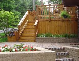 wood deck with brick paver patio and retaining wall planter