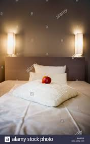 a red apple on a white pillow on a bed stock photo royalty free