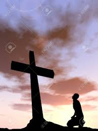conceptual religion black cross with a praying at sunset stock