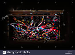 haphazard old fuse box with mess of wires cables colored coded running in
