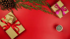 top view hands holding christmas presents on red background from