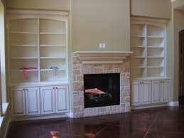 cream stone fireplace with cream shelves above between white