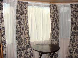 grey floral patterns of curtain fabric with white sheer curtain in