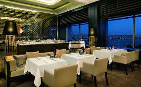 atelier real food the ritz carlton istanbul a dining room overlooking a river at night
