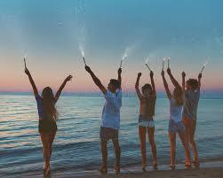 candele scintillanti amici sorridenti felici alla spiaggia con le candele scintillanti